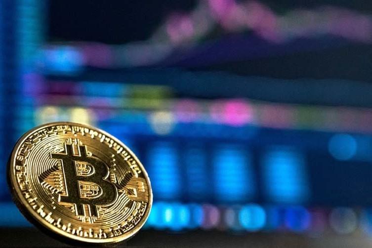 Bitcoin appoggiato davanti a un monitor