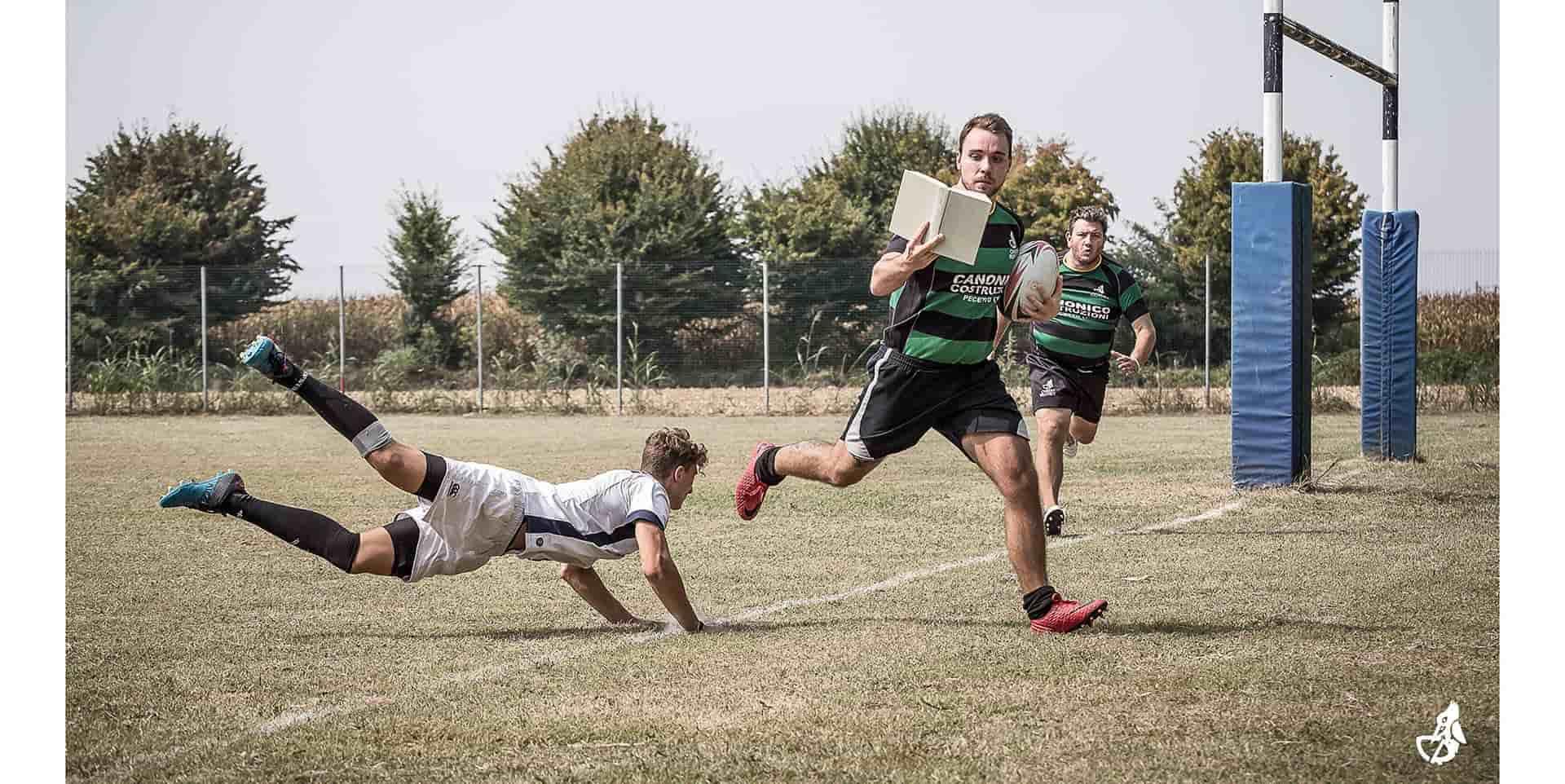 Rugbista del Chieri Rugby che corre verso la meta con la palla in mano leggendo un libro