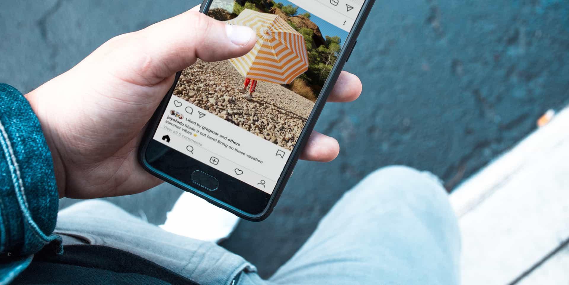 Un ragazzo guarda lo smartphone e scorre la bacheca di Instagram senza like