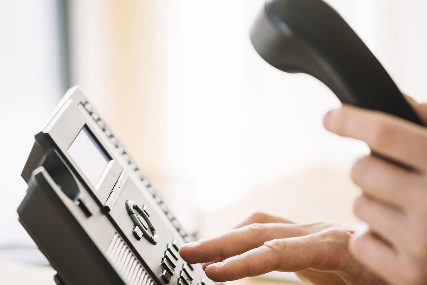 Un uomo fa un trasferimento di chiamata a un altro numero dal suo centralino telefonico in ufficio