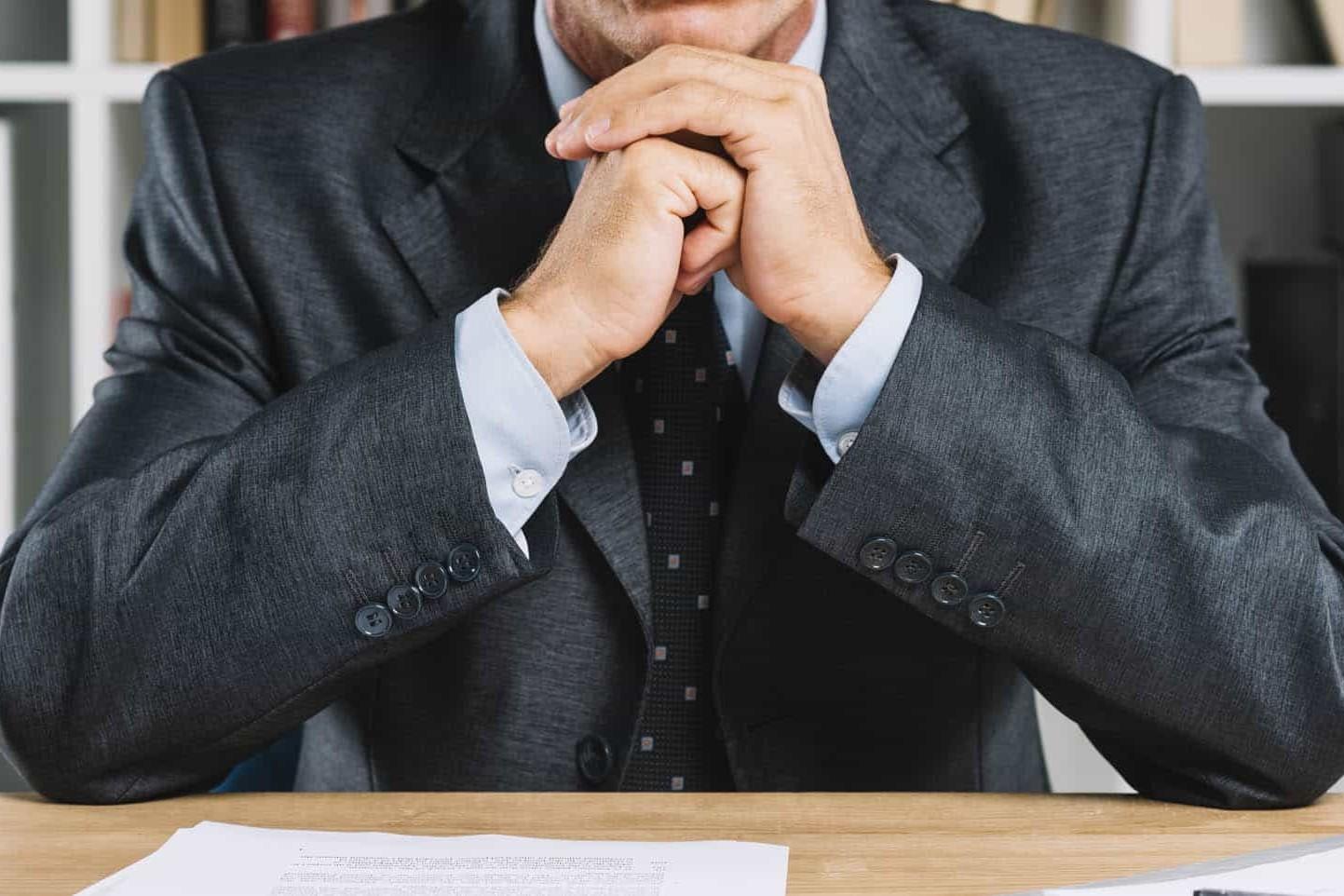 Imprenditore in giacca e cravatta seduto alla scrivania in atteggiamento pensieroso: soffre di solitudine dell'imprenditore