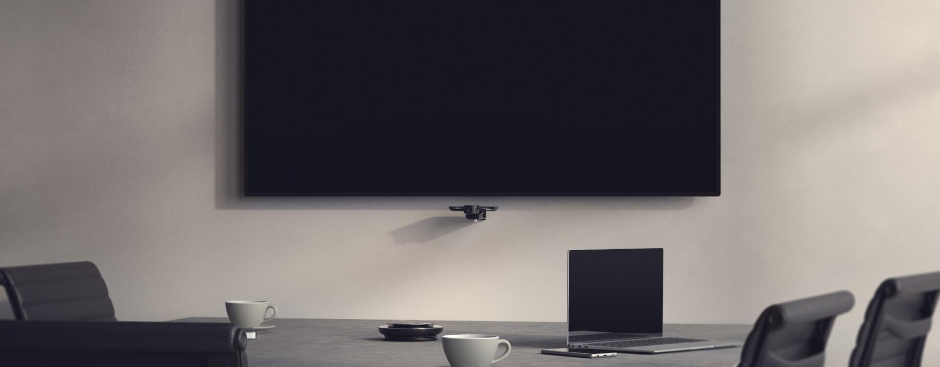 sala aziendale per le video conferenze ben attrezzata con un grande schermo grande, un microfono omnidirezionale e una webcam con tre telecamere